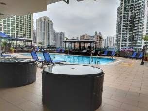 Four Points by Sheraton, hotel in Singapore off Robertson Quay. View of the pool against the Singapore River city skyline, condominiums, lounge chairs, verandah.