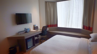 Four Points by Sheraton, hotel in Singapore off Robertson Quay. Seen here is the queen size bed, with couch by bay window, bedside table, TV, study desk, bar fridge