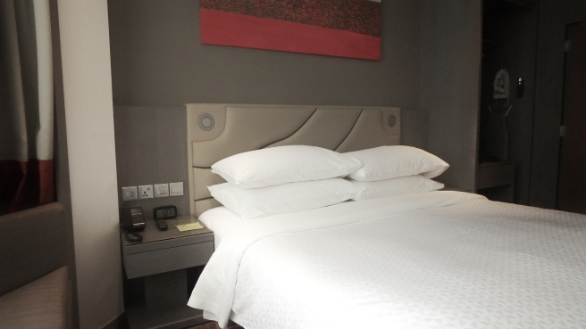Four Points by Sheraton, hotel in Singapore off Robertson Quay. Seen here is the queen size bed, with couch by bay window, bedside table and power points by the bed